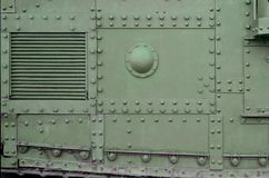 Texture of tank side wall, made of metal and reinforced with a multitude of bolts and rivets. Image of covering of a combat vehicle from the Second World War royalty free stock photo