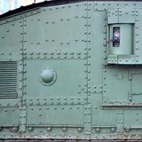 Texture of tank side wall, made of metal and reinforced with a multitude of bolts and rivets. Image of covering of a combat vehicle from the Second World War stock photography