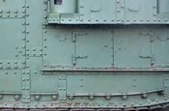 Texture of tank side wall, made of metal and reinforced with a multitude of bolts and rivets. Image of covering of a combat vehicle from the Second World War stock images
