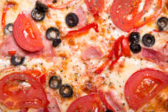 Texture of tasty Italian pizza with ham, tomatoes and olives Stock Photography