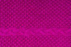 Texture tricotée par fuchsia lumineux fait main avec la tresse Photo stock