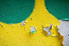 Texture of a two-color yellow and green old shabby concrete wall with bulbous peeling varicoloured paint, pits and patterns stock image