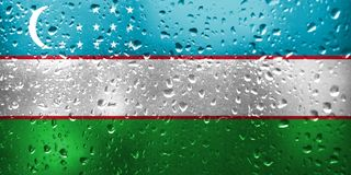 Texture of Uzbekistan flag on the glass. With drops of rain royalty free stock photo