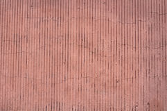 Texture of wall covered with pink stucco with vertical relief Royalty Free Stock Photo