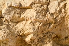 texture of a wall of sandy rock from a yellow friable old rotten stone of rock with shards, holes and layers of sand. The backgro royalty free stock images