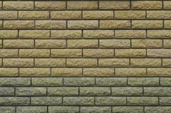 Modern weathered colored slate brick wall texture. The texture of the walls of the modern high-quality stone brick. Smooth texture of yellow brick wall in bright Stock Photo