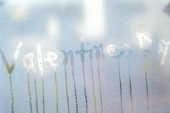 Texture of water droplets on clear window glass with Valentines Day text. In horizontal frame Stock Images