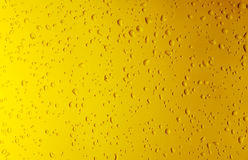 Texture water drops on the yellow bottle close-up as a background. Royalty Free Stock Photo