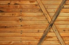 The texture of weathered wooden wall. Texture of an old fence of horizontal orange wooden planks with cross-board. S Stock Photos