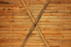 The texture of weathered wooden wall. Texture of an old fence of horizontal orange wooden planks with cross-board. S Stock Images