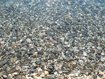 Texture of white and gray pebbles in the water Stock Photography
