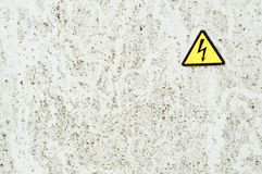 Texture of white iron metal rusty shabby painted paint spit wall yellow warning triangular danger high voltage sign. background stock photography