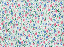 Texture white knitted fabric in small pink and blue flowers Royalty Free Stock Photo