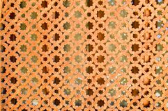 Texture of a wooden brown old man of an ancient beautiful carved textured Arabic Islamic Muslim window with ornaments and patterns. With holes in the form of Royalty Free Stock Image