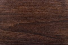 The texture of a wooden plate is nut-colored. Dark background for design use. royalty free stock image
