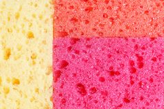 Colored sponges for washing dishes and other domestic needs. View from above. The texture of the yellow, red and orange sponges royalty free stock photos