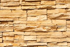 Texture of the yellow surface of a slate stone. Blocks of artificial finishing stone for wall decoration. Rough stone background