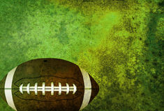 Textured American Football Field Background with Ball. A green textured American football field background with ball. Room for copy Royalty Free Stock Images
