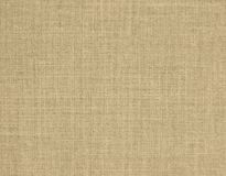 Textured background of beige natural textile. The textured background of beige natural textile for text, banner,logo, poster, label, sticker, layout, wallpaper stock photography