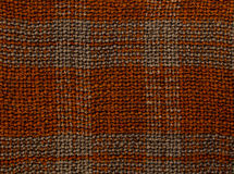 Textured background closeup. Knitted fabric brown in a cage. Textured background closeup. Knitted fabric brown in a cage, abstraction Royalty Free Stock Image