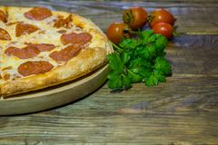 Italian Pepperoni pizza with salami on dark wooden background. Italian traditional food. A textured background. Copy paste place Stock Image
