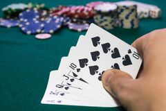 A close up image of stacked poker chips and a royal flush. A textured background.Copy paste place Stock Image