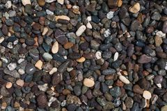 Textured background from dark smooth sea pebbles Royalty Free Stock Photos