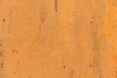 Textured background of a faded yellow paint with rusted cracks on rusted metal. Grunge texture of an old cracked metal. Textured background of a faded yellow Stock Images