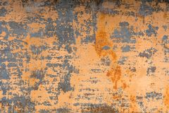 Textured background of a faded yellow paint with rusted cracks on rusted metal. Grunge texture of an old cracked metal. Textured background of a faded yellow Stock Image