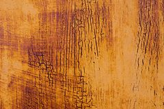 Textured background of a faded yellow paint with rusted cracks on rusted metal. Grunge texture of an old cracked metal. Textured background of a faded yellow Royalty Free Stock Photo