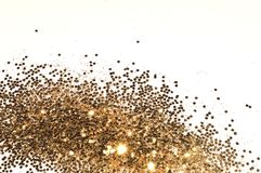 Textured background with golden glitter sparkle on white, decorative spangles in nostalgic colors.  Royalty Free Stock Photo
