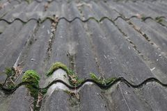 Textured background of old asbestos roof sheets. Texture of gray fiber cement roof sheet, closeup. Pattern of weathered old roof, rustic background Stock Photos