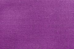Textured background rough fabric of lilac color. The textured background or wallpaper from rough fabric of lilac color and a blank space Stock Photo