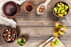 Textured background with salted olives of several varieties. And kitchen utensils, copy space Stock Photos
