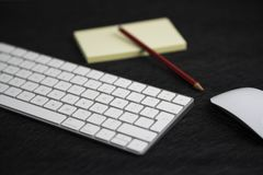 Textured black board with a pencil on a paper, a keyboard and a mouse royalty free stock photo