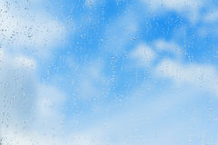 Textured blue background of sky, natural water drops on window glass, rain texture. Concept of clear, pure, bright Royalty Free Stock Photos