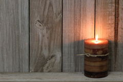 Textured candle lit against wood background Royalty Free Stock Images