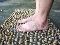 Textured cement  paved with stones and Foot Massage Royalty Free Stock Photography