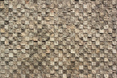 Textured checkered background of relief stone mosaic on a wall Royalty Free Stock Images