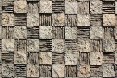 Textured checkered background of relief stone mosaic on a wall Stock Images