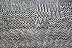 Textured checkered background of relief stone mosaic on wall Stock Photos