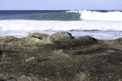 Textured Coastal Rock Bed With Breaking Waves royalty free stock image