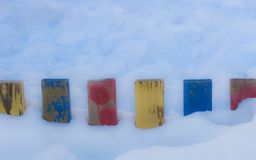 Textured Colorful Painted Blue, Red, Yellow Wooden Picket Fence Planks In Deep Snow, Colorful Rustic Style Background For Vintage stock image