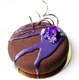 Dark chocolate cake with purple mirror glaze and spring flowers royalty free stock image