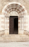 Textured door with stone arch. Old church textured door with stone arch facade Stock Images