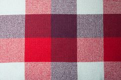 Textured fabric with a pattern of squares of shades of red, purple and white. Colour Stock Photos