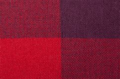 Textured fabric with a pattern of squares of shades of red. And purple Stock Image