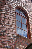 Textured Face Brick Wall of Tower With Arched Window Frame Royalty Free Stock Photos