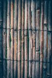 Textured fence made of thin wooden sticks aged and weathered. Na. Tural background of wooden rails in a vertical row royalty free stock photography