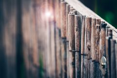 Textured fence made of thin wooden sticks aged and weathered. Na. Tural background of wooden rails in a vertical row royalty free stock image